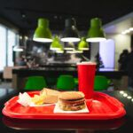 A hamburger, soft drink, and french fries on top of a quick-service food tray.