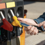 A photo of a man using a mobile phone to make a contactless payment at the gas pump.