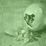 Costs of chargebacks: A photo of a piggy bank smashed open, with coins spilling out.