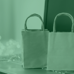 A photo of a pair of paper shopping bags on top of an open laptop, surrounded by holiday lights.
